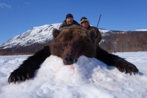 Hunter with outfitter and the brown bear