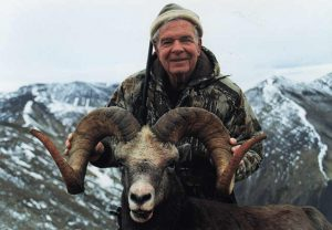 Hunter with his snow sheep trophy in snowy mountains of Magadan, Russia with Kulu Safaris
