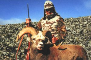 Hunter with a rifle and his trophy in the mountains of Magadan, Russia, Kulu Safaris